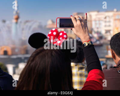 Woman taking pictures with iPhone of a show at Tokyo Disneysea theme park. Japan. - Stock Photo