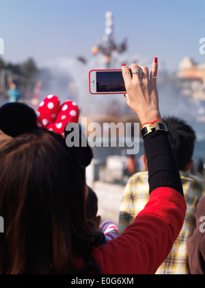 Woman recording a show with her iPhone at Tokyo Disneysea theme park. Japan. - Stock Photo