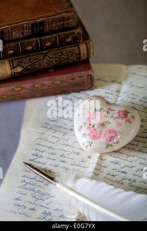 a quill on an old letter with books - Stock Photo
