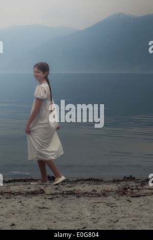 a girl in a dress is dancing at the lake - Stock Photo