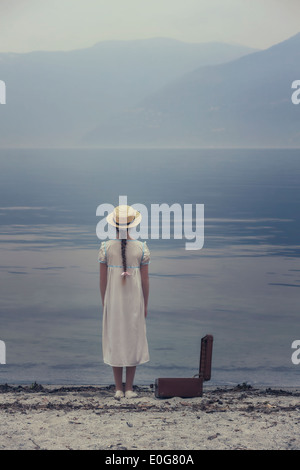 a girl at a lake with an open suitcase - Stock Photo