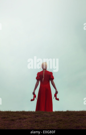 a girl in a red dress on a meadow with her shoes in her hands - Stock Photo