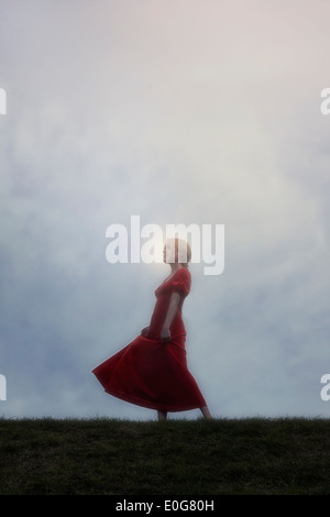 a woman in a red dress is dancing on a meadow - Stock Photo