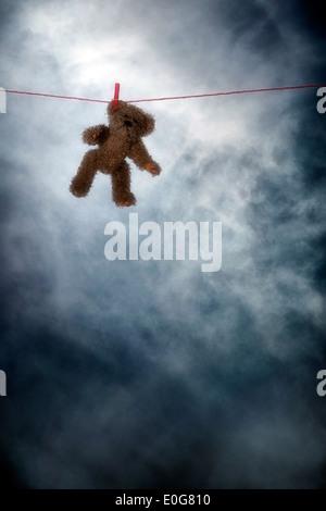 a teddy bear on a clothes line - Stock Photo