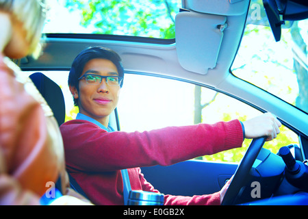 Happy couple in a car with sun shining through the window - Stock Photo