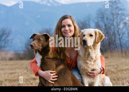Young woman with dogs, Upper Bavaria, Germany, Europe - Stock Photo