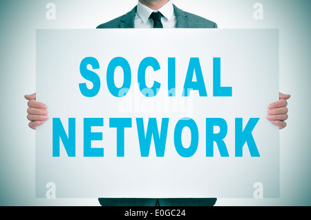 man wearing a suit showing a signboard with the text social network written in it - Stock Photo