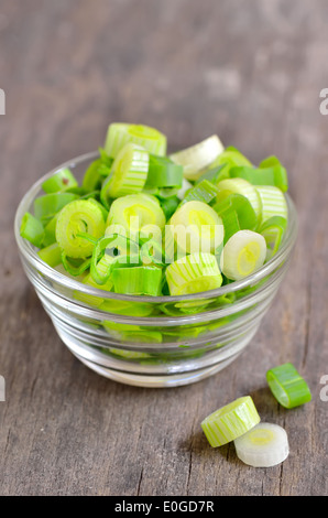 chopped green onion in glass bowl isolated on wooden table - Stock Photo