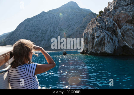 Woman looking towards the coast, sailing along the lycian coast, Ceneviz bay near Cirali, Lycia, Mediterranean Sea, - Stock Photo