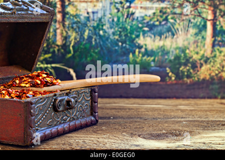 Dried red chilli flakes on rustic wooden table - Stock Photo