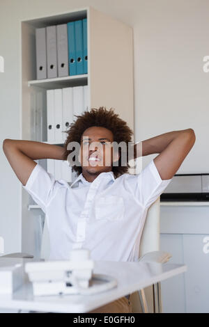 Relaxed casual businessman leaning back at his desk - Stock Photo