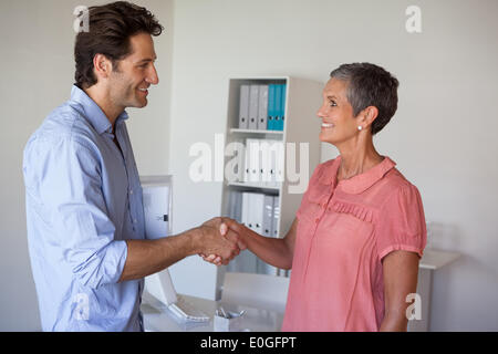 Casual smiling business people shaking hands - Stock Photo