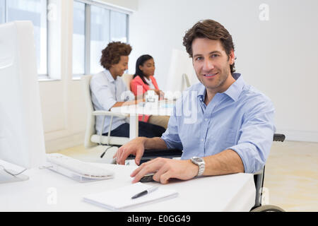 Man in wheelchair works hard looking at camera - Stock Photo