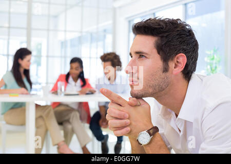 Serious businessman sitting and contemplating - Stock Photo