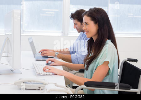 Worker in wheelchair working on computer - Stock Photo