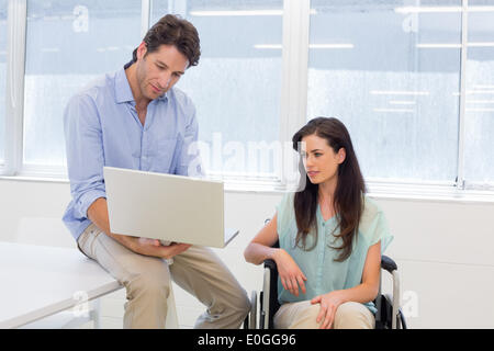Businessman showing woman in wheelchair the laptop - Stock Photo