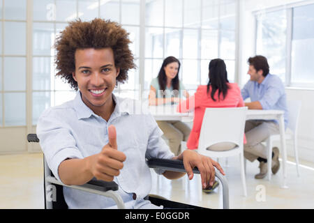 Businessman in wheelchair gives thumbs up to camera - Stock Photo