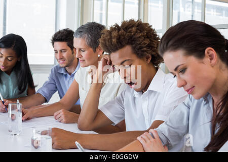 Yawning casual businessman in a meeting - Stock Photo