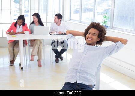 Businessman relaxing with coworkers behind him - Stock Photo