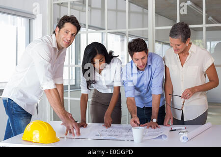 Team of architects going over blueprints with one smiling at camera - Stock Photo