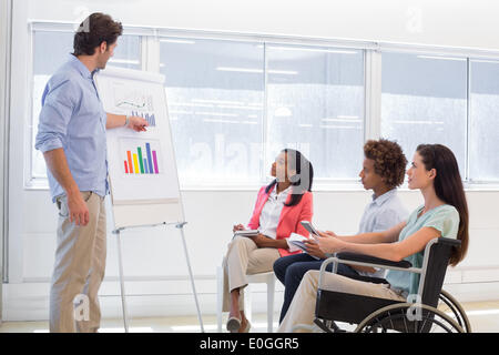 Attractive businessman presenting graph to coworkers - Stock Photo