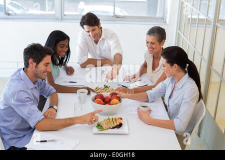 Business people eating sandwiches and fruit for lunch - Stock Photo