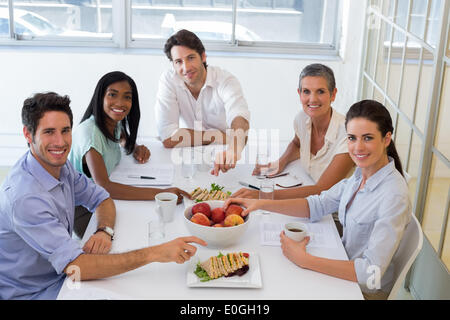 Business people smiling at camera eating sandwiches and fruit for lunch - Stock Photo