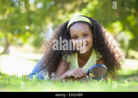 Young girl holding magnifying glass in the park smiling at camera - Stock Photo
