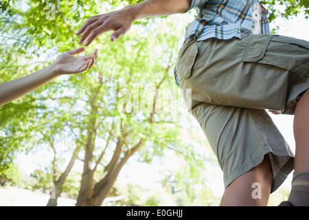 Man giving helping hand to girlfriend on hike - Stock Photo