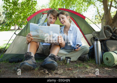 Cute couple sitting by tent reading a map - Stock Photo