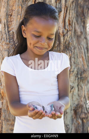 Little girl holding a butterfly in the park - Stock Photo
