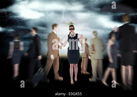 Composite image of redhead businesswoman in a blindfold - Stock Photo