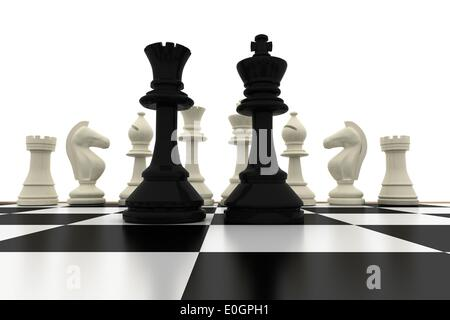 Black king and queen standing in front of white pieces - Stock Photo
