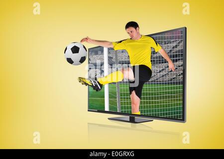 Football player kicking ball through tv - Stock Photo