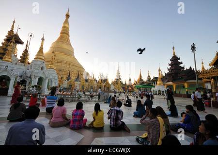 People praying in front of the Shwedagon Pagoda, Yangon, Myanmar, Burma, Asia - Stock Photo