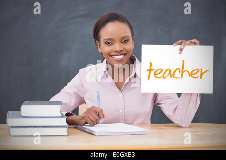 Happy teacher holding page showing teacher - Stock Photo