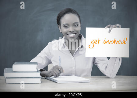 Happy teacher holding page showing get involved - Stock Photo