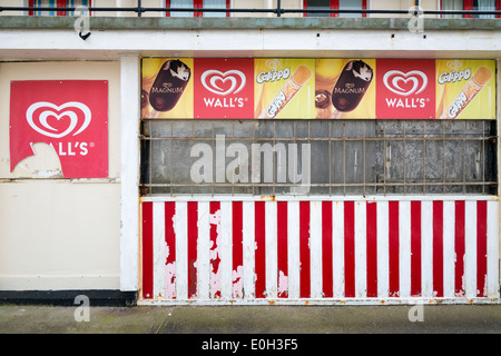 A closed and run down Wall's Ice cream parlour or kiosk on the promenade of the seaside town of Sheringham Norfolk - Stock Photo