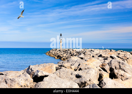 Bay on the coast at Gruissan with large rocks as a breakwater on the Mediterranean Sea with sailboats on the horizon. - Stock Photo