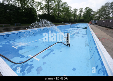 A man filling an outdoor swimming pool with a hose stock photo royalty free image 69220832 alamy for Jesus green swimming pool cambridge