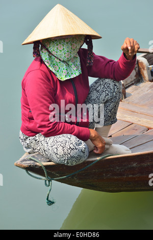 Vietnamese woman sits on the stern of her river boat waiting for tourists to take rides on the river in Hoi An,Vietnam - Stock Photo