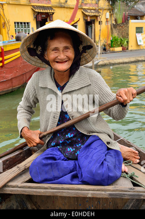 Elderly smiling Vietnamese woman taking tourists for  rides on the river in the town of Hoi An, Vietnam paddling - Stock Photo