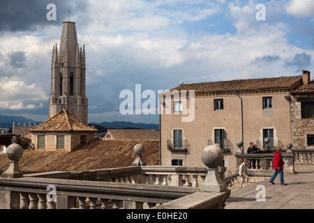 Tourists outside Cathedral of Saint Mary of Girona, Catalonia, Spain. Basilica Parroquial de Sant Feliu in the background - Stock Photo