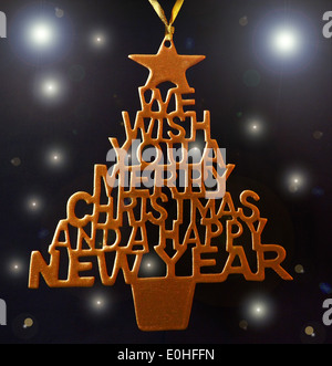 We Wish You A Merry Christmas And A Happy New Year tree. Hand fretted Christmas decoration spray painted gold - Stock Photo