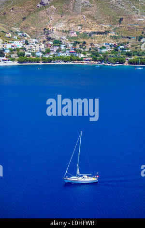 White yacht on blue sea, bay with surrounding hills, Greece - Stock Photo