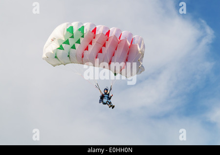 One day with parachutist in airfield. The girl skydiver landing under multicolor parachute. - Stock Photo