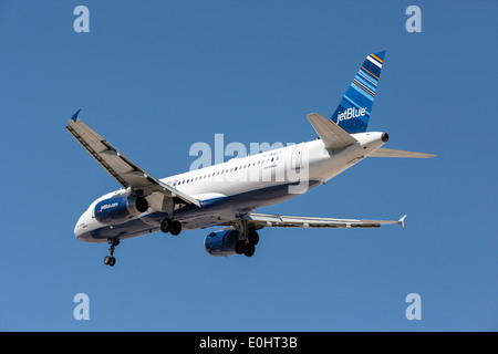 An Airbus A320 of JetBlue on final approach - Stock Photo