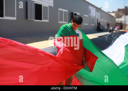 Gaza, Palestinian Territories. 14th May, 2014. Palestinians hold a large Palestinian flag during a rally ahead of - Stock Photo