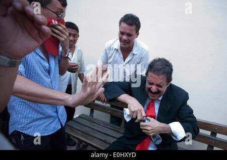 Tegucigalpa, Honduras. 13th May, 2014. The former Honduran President Manuel Zelaya (R) reacts after affected by tear gas and being evacuated with his followers from the National Congress, in Tegucigalpa, Honduras, on May 13, 2014. Followers and deputies of the Liberty and Refoundation Party (Libre, for its acronym in Spanish), the second political force in Honduras, broke in the National Congress on Tuesday, after clashing with police elements that guarded the Legislative Palace. Credit:  Rafael Ochoa/Xinhua/Alamy Live News
