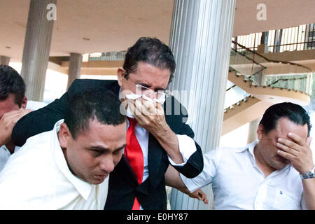 Tegucigalpa, Honduras. 13th May, 2014. The former Honduran President Manuel Zelaya (C) covers his face from tear gas after being evacuated with his followers from the National Congress, in Tegucigalpa, Honduras, on May 13, 2014. Followers and deputies of the Liberty and Refoundation Party (Libre, for its acronym in Spanish), the second political force in Honduras, broke in the National Congress on Tuesday, after clashing with police elements that guarded the Legislative Palace. Credit:  Rafael Ochoa/Xinhua/Alamy Live News